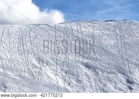 Snowy Off-piste Slope For Freeride With Traces From Skis, Snowboards And Beautiful Sky With Clouds A