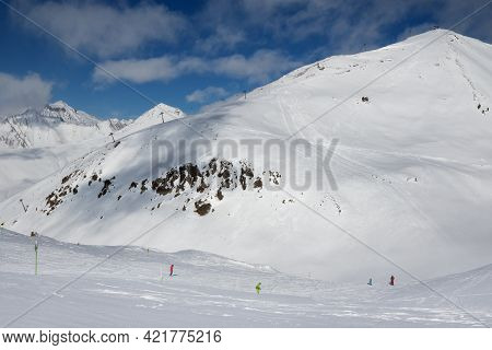 Skiers And Snowboarders Downhill On Freeride Trace And Mountains With Clouds At Sun Cold Day. Caucas