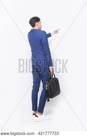 full length young businessman,wearing in blue suit ,tie with striped shirt ,tie and blue pants , white shoes holding handbag with finger to side