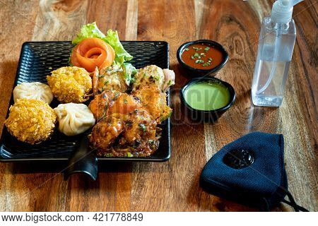 Top Down Shot Of Indian Chinese Tibetan Fried Roasted Tandoori Momos With Sauces Served With Sanitiz