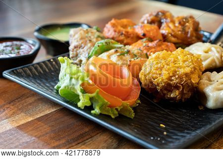 Close Up Shot Of Tandoori Fried Steamed Momos With Tartar Mint Sauce Placed On A Black Plate On A Wo