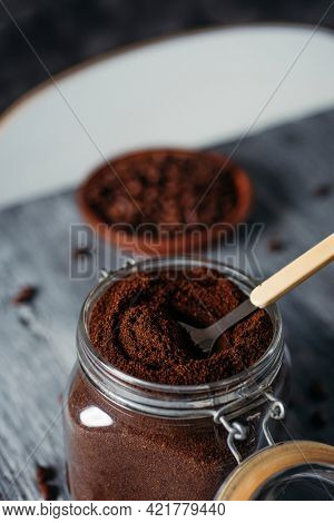 closeup of a hermetic glass jar full of ground coffee on a gray rustic wooden table
