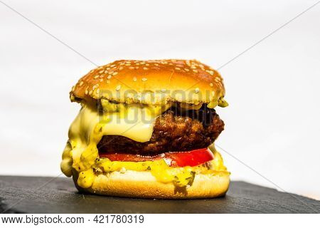 Detail Of Fresh Tasty Beef Cheeseburger With Melted Cheese Isolated On White Background