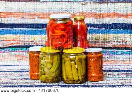 Glass Jars With Pickled Red Bell Peppers And Pickled Cucumbers (pickles) Isolated. Jars With Variety