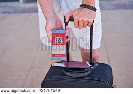 Suitcase And Smartphone In Hand Displaying On App Mobile Expired Digital Vaccination Certificate For