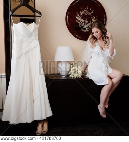 Bride In A White Silk Robe Sits On The Table Near The Wedding Dress On A Hanger.