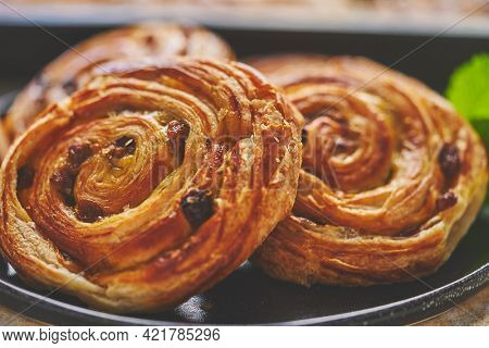 Close up of Sweet cinnamon roll cake with raisins filling served on the black plate