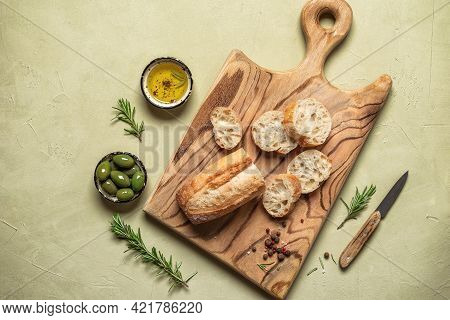 Fresh Ciabatta Slices On A Wooden Board With Olive Oil, Olives And Rosemary. Beige Concrete Backgrou