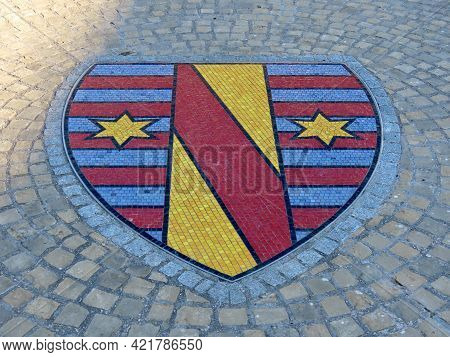 Vitchen Town Coat Of Arms As A Mosaic On Cobbled Street. Vitchen, Luxembourg - March 3, 2021