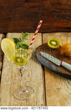 Cocktail With Kiwi Mint And Lemon In A Glass On A Wooden Table Next To Lemon And Kiwi On A Board. Ve