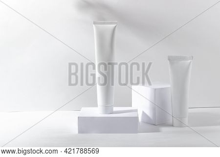 White Cosmetic Jar On A Stand With Shadows. Toothpaste, Face And Body Cream. Professional Cosmetics