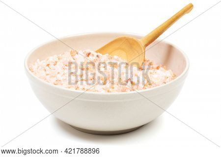 Red coarse Himalayan salt in a bowl with wooden shovel isolated on white background