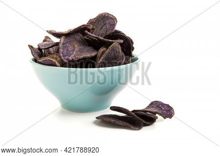 Potato chips made from purple potatoes in a turquoise bowl isolated on white background