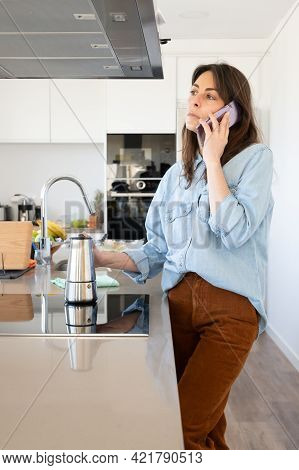 Successful Businesswoman Talking On The Phone In The Elegant Kitchen Of Her Home.lifestyle