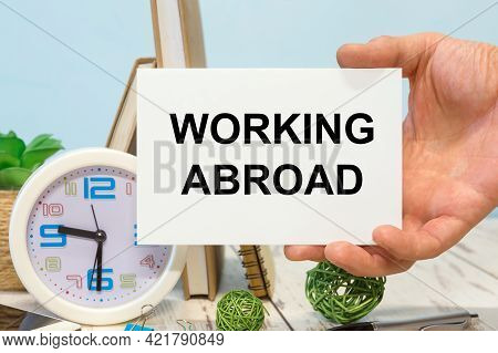 Working Abroad - Text On A Card In Your Hand Next To Office Supplies