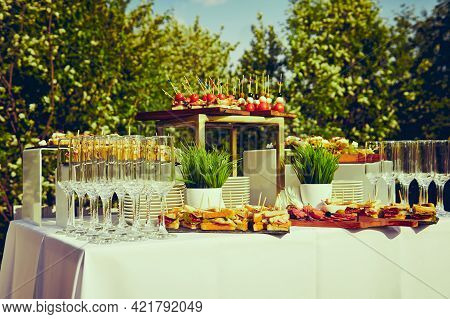 Buffet In The Open Air - A Table With Canapes And Glasses Against The Background Of Flowering Trees