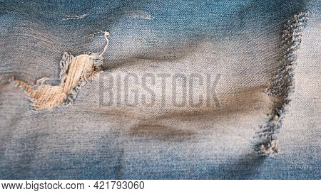 Denim Background In Blue Fabric With Distressed Takani. Blue Ripped Jeans Close-up. Denim Stylish. T