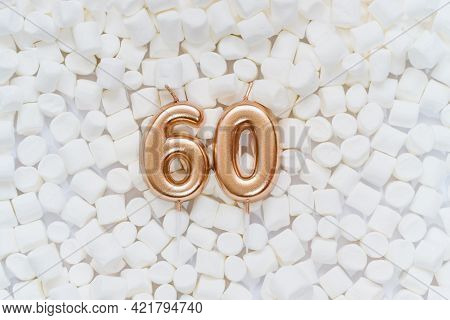 Number 60 Golden Celebration Birthday Candle On Background With White Marshmallows. Sixty Years Birt