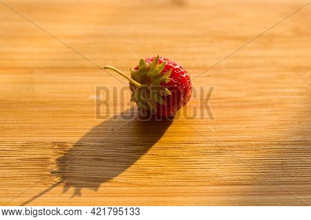 Ripe Fresh Strawberries On Bamboo Wooden Background With Long Shadow, Close Up.