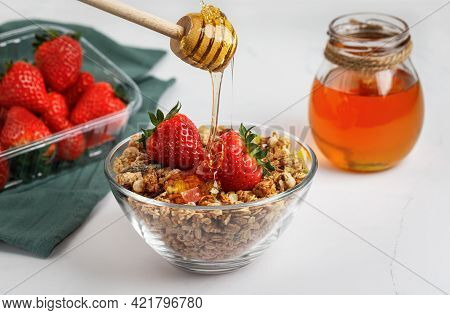 Muesli With Strawberries And Honey In A Glass Plate, Isolated On A White Background. A Honey Stick.