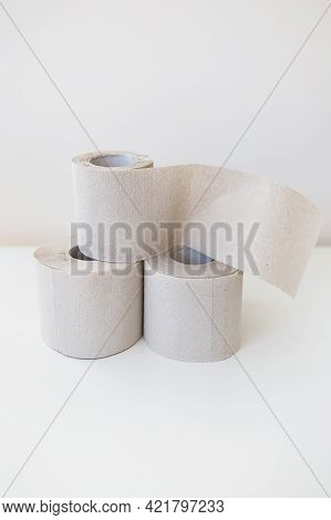 A Couple Of Rolls Of Gray Toilet Paper Are Standing On A White Table. Hygiene And Cleanliness Concep