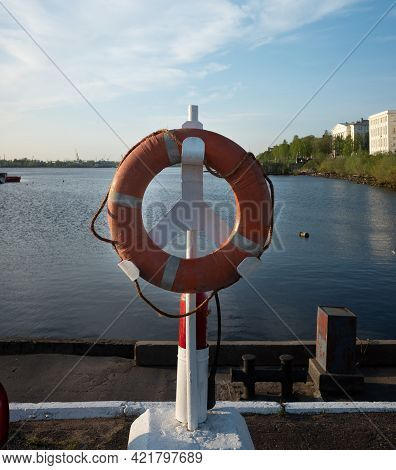 A Life Preserver Hangs On The Pier On The River Bank. Copy Space.