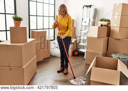 Middle age blonde woman smiling happy cleaning new home using mop.