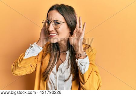 Young beautiful woman wearing business style and glasses trying to hear both hands on ear gesture, curious for gossip. hearing problem, deaf