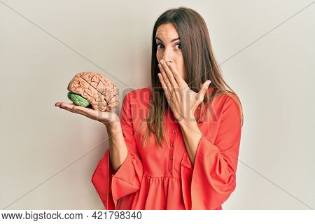 Young beautiful woman holding brain covering mouth with hand, shocked and afraid for mistake. surprised expression