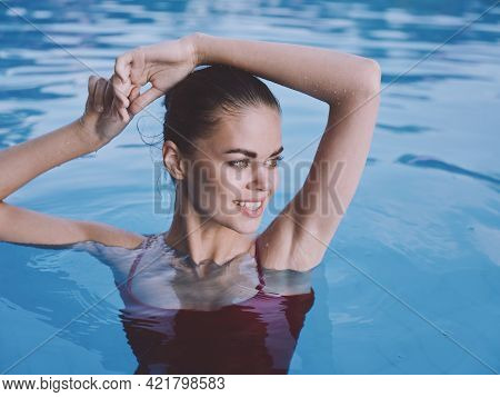 Woman In Red Swimsuit In The Pool Holds Her Hand On Her Head