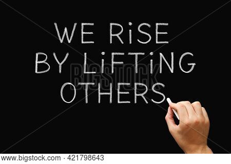 Hand Writing We Rise By Lifting Others With Chalk On Blackboard. Teamwork, Leadership, Altruism, Or