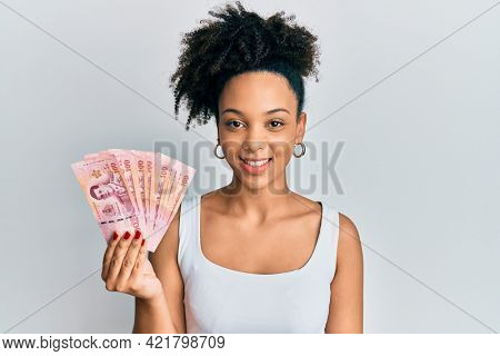 Young african american girl holding thai baht banknotes looking positive and happy standing and smiling with a confident smile showing teeth