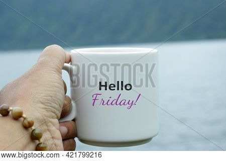 Friday Coffee. Hello Friday Greeting Text On A White Cup Of Coffee Or Tea On Blue Lake Nature Backgr
