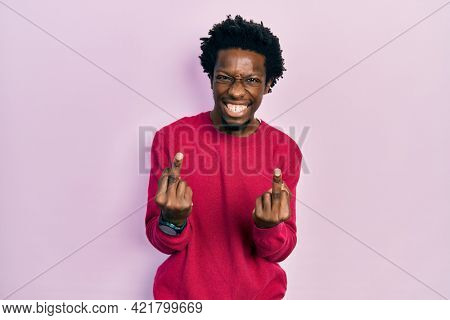 Young african american man wearing casual clothes showing middle finger doing fuck you bad expression, provocation and rude attitude. screaming excited