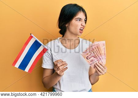 Young caucasian woman holding thailand flag and baht banknotes angry and mad screaming frustrated and furious, shouting with anger. rage and aggressive concept.