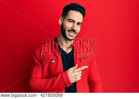 Young hispanic man wearing red leather jacket pointing aside worried and nervous with forefinger, concerned and surprised expression