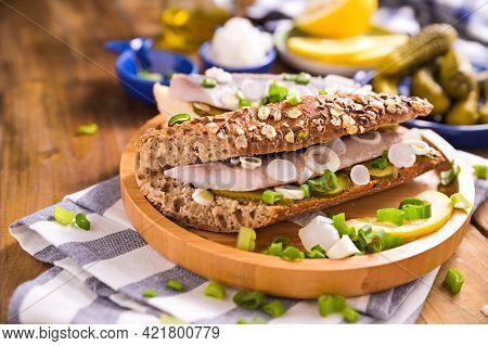 Dutch Herring In A Sandwich In Grain Bread With Fresh Green Onions. Toast With Dutch Herring, Onions