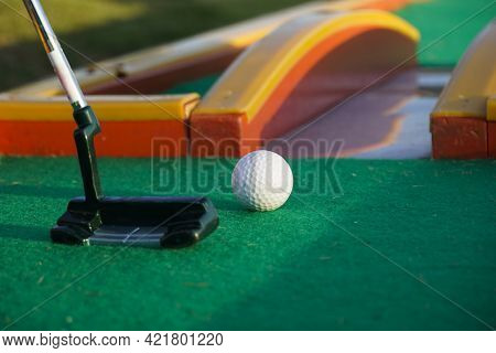 Golf Club And Golf Ball Close Up In Grass Field With Sunset. Golf Ball Close Up In Golf Coures
