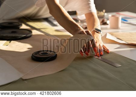 Dressmaking Process In Atelier: Female Tailor Drafting Clothes Model On Fabric For Cutting Patterns
