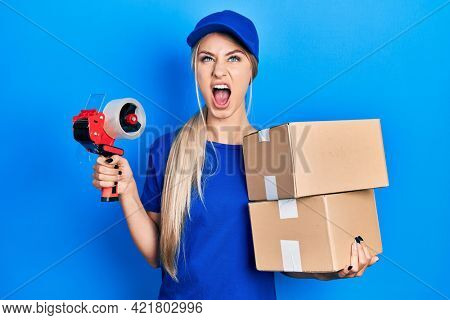 Young caucasian woman holding packages and packing tape angry and mad screaming frustrated and furious, shouting with anger looking up.