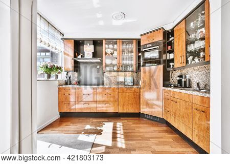 Spacious Kitchen Room With Wooden Cabinets And Black Elements And Wooden Parquet Flooring In Bright