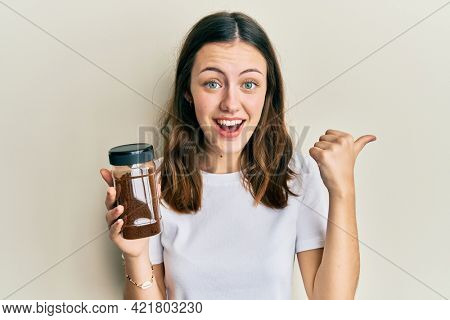 Young brunette woman holding soluble coffee pointing thumb up to the side smiling happy with open mouth