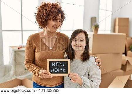 Mature mother and down syndrome daughter moving to a new home, standing by cardboard boxes holding blackboard with new home phrase
