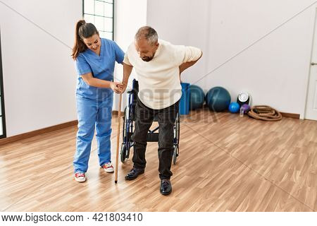 Senior man sitting on wheelchair being assited by geriatric nurse, handicapped mature man getting help to stand up