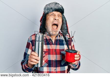 Handsome mature handyman wearing winter hat with ear flaps drinking hot coffee from thermo angry and mad screaming frustrated and furious, shouting with anger looking up.