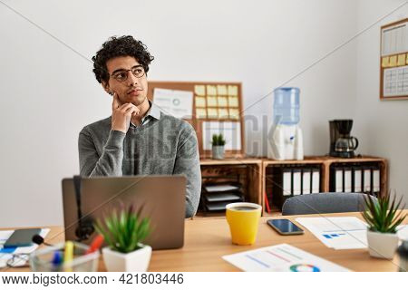 Young hispanic man wearing business style sitting on desk at office with hand on chin thinking about question, pensive expression. smiling with thoughtful face. doubt concept.