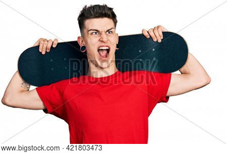 Young caucasian boy with ears dilation holding skate over shoulders angry and mad screaming frustrated and furious, shouting with anger looking up.