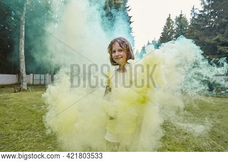 A Beautiful Girl Lets Out Yellow Colored Smoke, Smiles And Looks At The Camera.