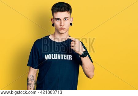 Young caucasian boy with ears dilation wearing volunteer t shirt pointing with hand finger to the side showing advertisement, serious and calm face
