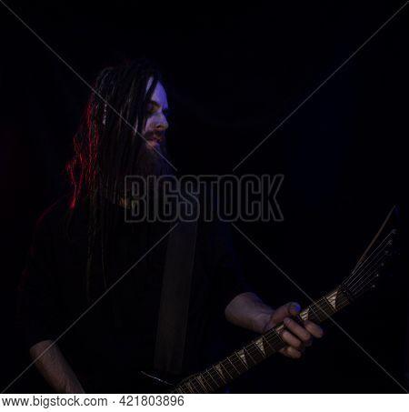 Brutal Guitarist With Black Guitar Over Dark